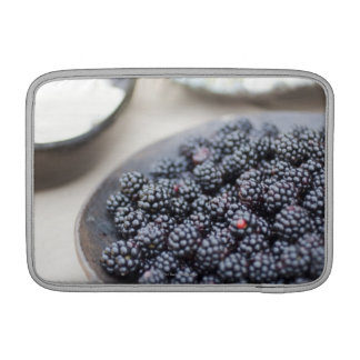 Bowl of blackberries on a table sleeve for MacBook air