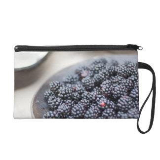 Bowl of blackberries on a table wristlet