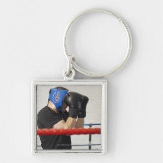 Boxeador que cubre su cara en anillo llavero cuadrado plateado