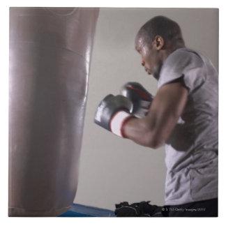 Boxeador que usa el saco de arena en gimnasio azulejo cuadrado grande