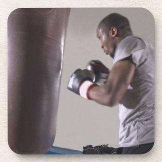 Boxeador que usa el saco de arena en gimnasio posavaso