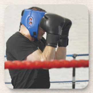 Boxer covering his face in ring beverage coasters
