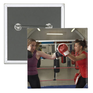 Boxer training with coach in gym buttons