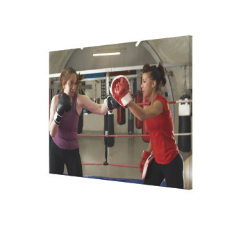 Boxer training with coach in gym canvas print