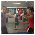 Boxer training with coach in gym tile
