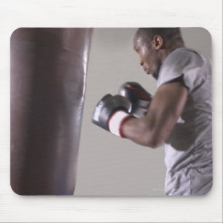 Boxer using punching bag in gym mouse pad