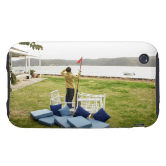 Boy (10-11) standing in imaginary boat made of iPhone 3 tough case