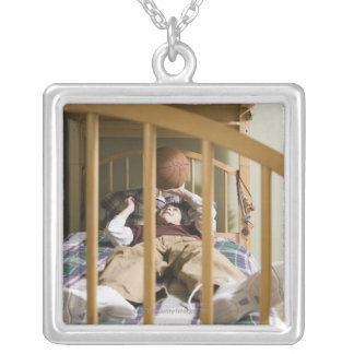 Boy (11-13) lying on bed, playing with pendants