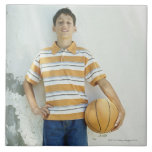 Boy (12-13) standing in front of white large square tile