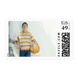 Boy (12-13) standing in front of white postage stamp