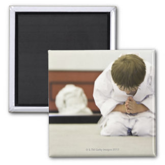 Boy (4-5 years) wearing karate outfit bowing, magnet