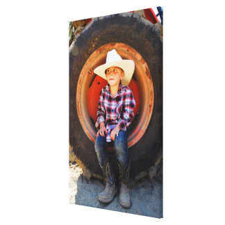 Boy (4-7) yrs old, sitting in tractor tire. canvas print