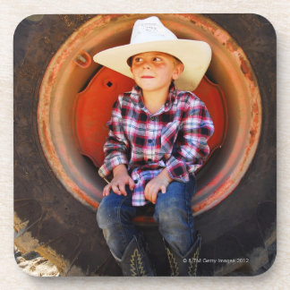 Boy (4-7) yrs old, sitting in tractor tire. coaster