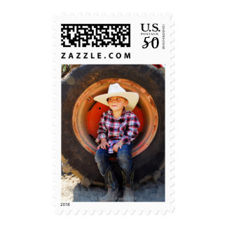 Boy (4-7) yrs old, sitting in tractor tire. postage