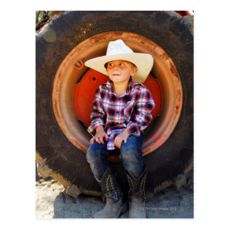 Boy (4-7) yrs old, sitting in tractor tire. postcard
