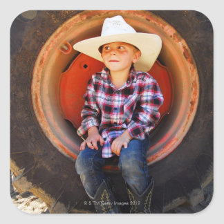 Boy (4-7) yrs old, sitting in tractor tire. square sticker