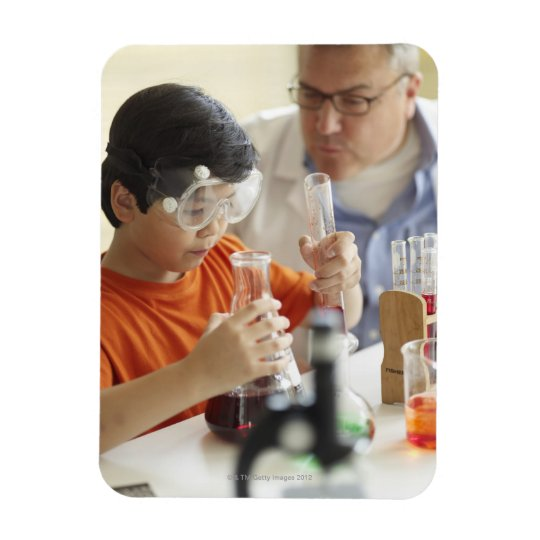 Boy (6-7) and teacher in chemistry class magnet