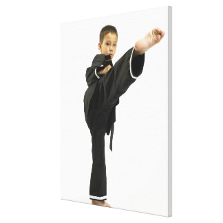 Boy (6-8) in karate outfit kicking canvas print