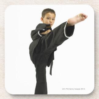 Boy (6-8) in karate outfit kicking coaster