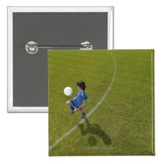 Boy (8-10) footballer practicing skills, button