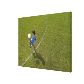 Boy (8-10) footballer practicing skills, stretched canvas print
