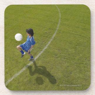 Boy (8-10) footballer practicing skills, coaster