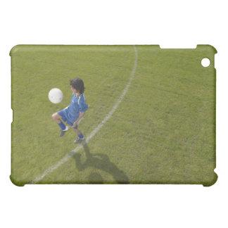 Boy (8-10) footballer practicing skills, iPad mini covers