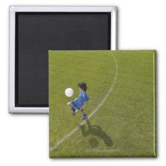 Boy (8-10) footballer practicing skills, magnet