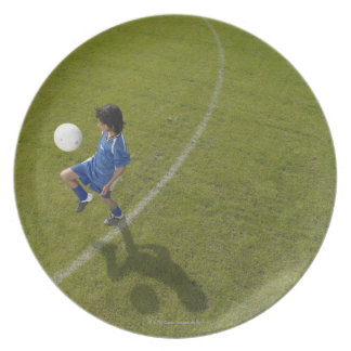 Boy 8-10 footballer practicing skills party plate