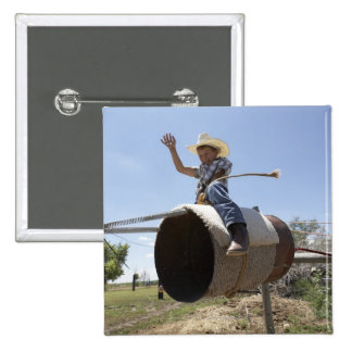 Boy (8-10) riding makeshift rodeo bull 2 inch square button