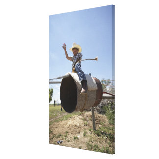 Boy (8-10) riding makeshift rodeo bull canvas print