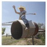 Boy (8-10) riding makeshift rodeo bull ceramic tile