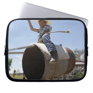 Boy (8-10) riding makeshift rodeo bull laptop sleeve