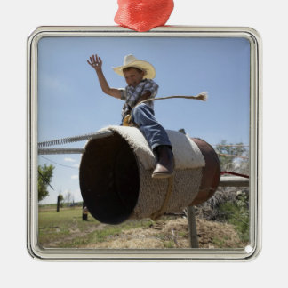 Boy (8-10) riding makeshift rodeo bull metal ornament