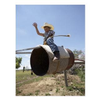 Boy (8-10) riding makeshift rodeo bull postcard