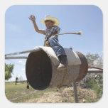Boy (8-10) riding makeshift rodeo bull square sticker