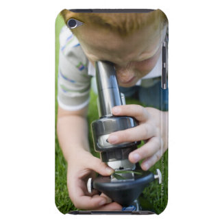 Boy (8-9) using light microscope, close-up barely there iPod case
