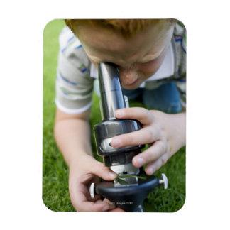 Boy (8-9) using light microscope, close-up magnet