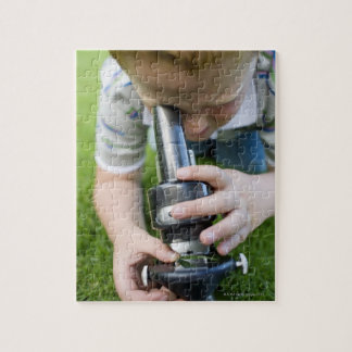 Boy (8-9) using light microscope, close-up jigsaw puzzles