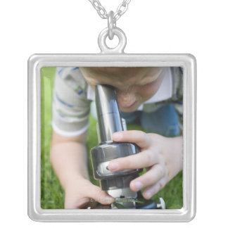 Boy (8-9) using light microscope, close-up silver plated necklace