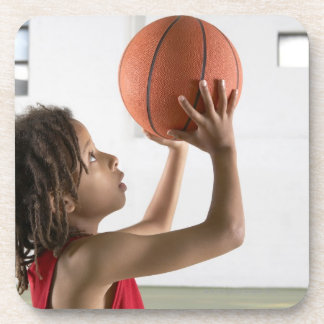 Boy aiming a shot with a basketball in a school coaster