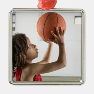 Boy aiming a shot with a basketball in a school metal ornament