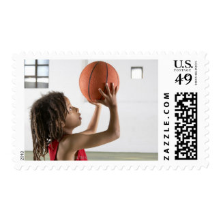 Boy aiming a shot with a basketball in a school postage stamp