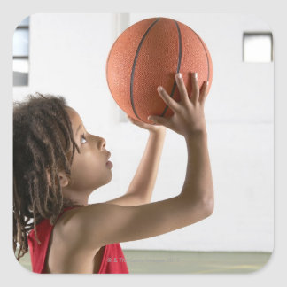 Boy aiming a shot with a basketball in a school square stickers