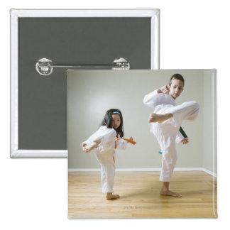 Boy and girl (4-9) practising Taekwondo kicks Pinback Button