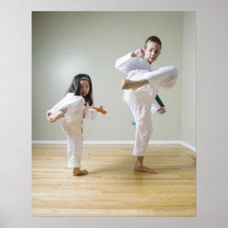 Boy and girl (4-9) practising Taekwondo kicks Poster