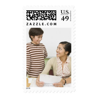 Boy and teacher at teachers desk postage stamp
