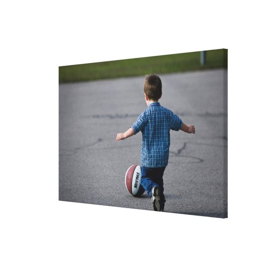 Boy chasing basketball outdoors canvas print