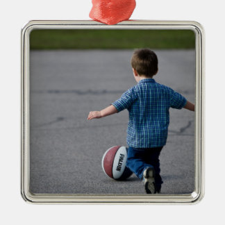 Boy chasing basketball outdoors metal ornament