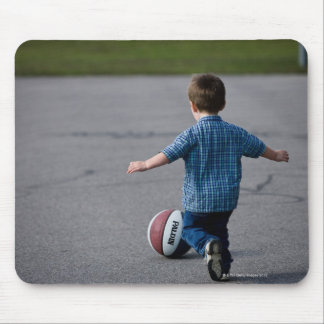 Boy chasing basketball outdoors mouse pad